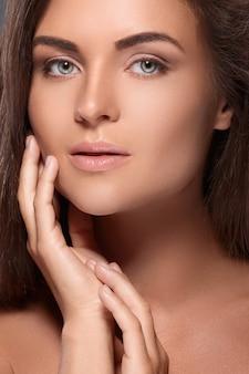 完璧な眉の形と裸のメイクアップを持つ美しい女性