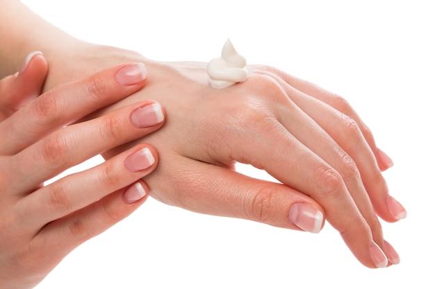 Женщина, применяя увлажняющий крем на руках