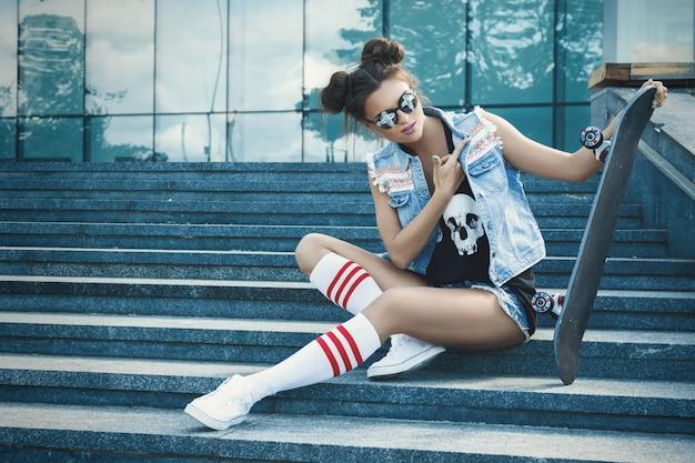 路上でスケートボードとスタイリッシュな女の子