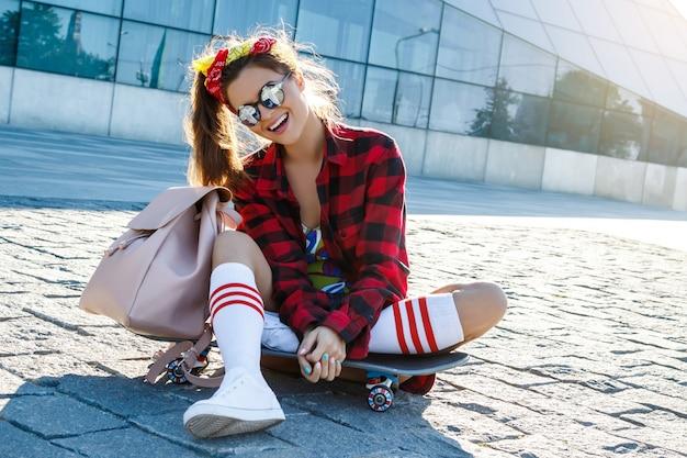Стильная девушка со скейтбордом на улице