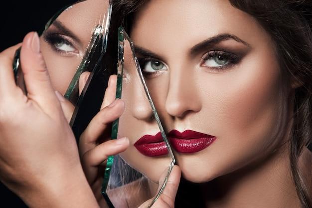 鏡の破片を持つ美しい女性
