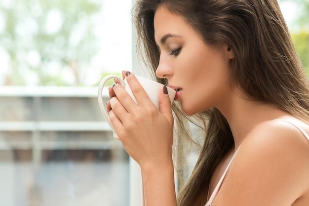 Красивая женщина пьет кофе или чай