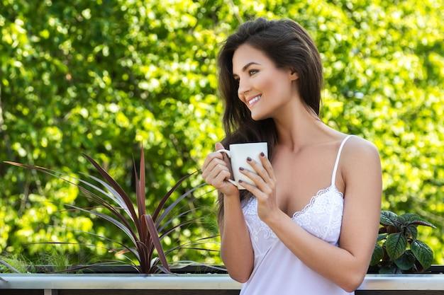 Счастливая женщина пьет кофе на балконе или в саду
