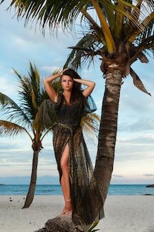 Женщина в красивом платье с леопардовым принтом на пляже