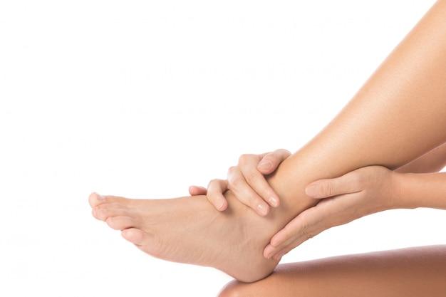 女性は負傷した足首に触れています