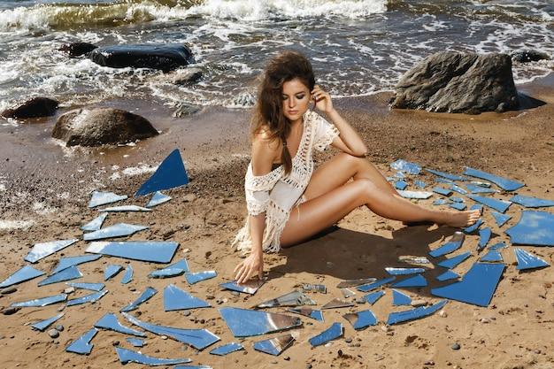 Женщина на пляже с осколками зеркала