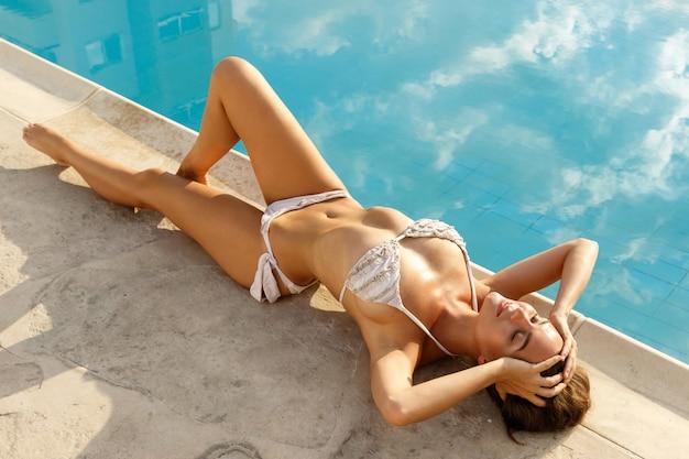 スイミングプールの横に横たわっている美しい女性