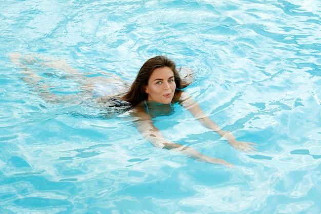 幸せな女は、スイミングプールで泳ぐ