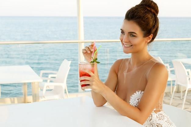 カクテルのグラスと美しいドレスの女性