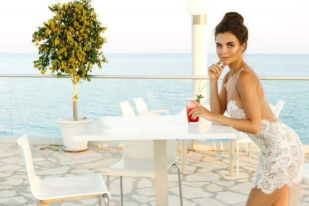 Женщина в красивом платье с бокалом коктейля
