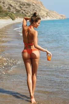 カクテルのグラスとビーチで女性