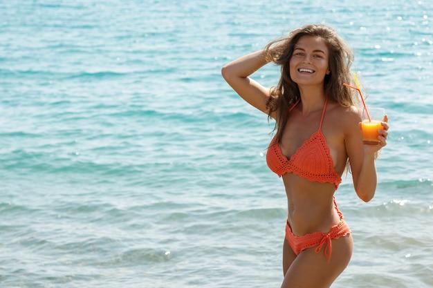 Женщина на пляже с бокалом коктейля