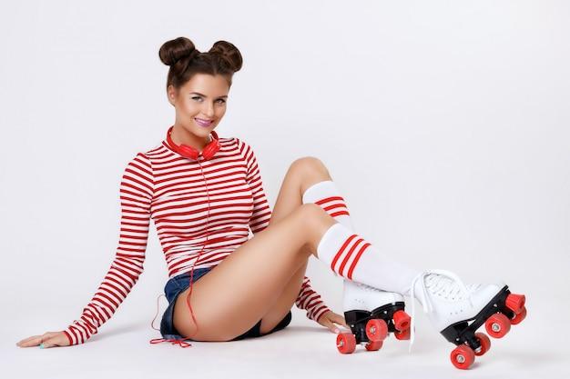 ローラースケートと赤いヘッドフォンで美しい女性