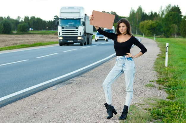 道路のヒッチハイカーは空白の段ボールの看板を持っています