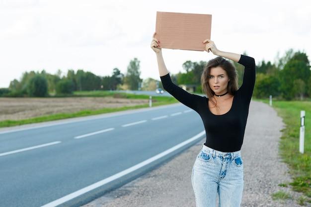 Автостопщик на дороге держит пустой картонный знак