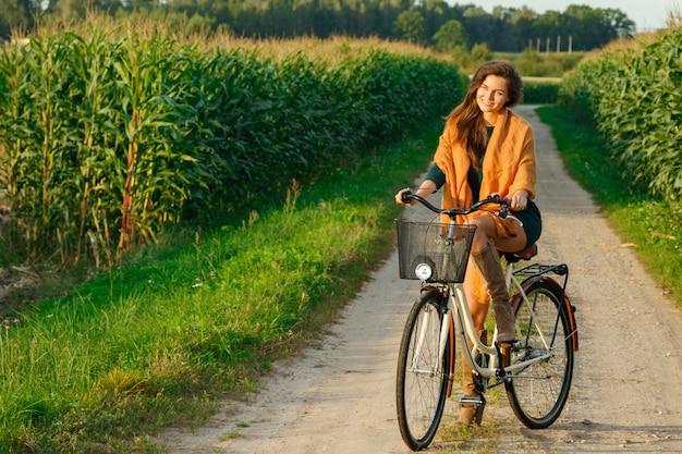 トウモロコシ畑の田舎道で女性がサイクリング