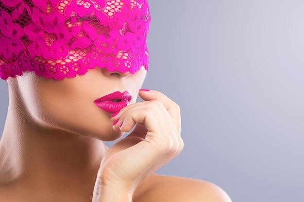 彼女の顔にピンクの目隠しを持つ女性