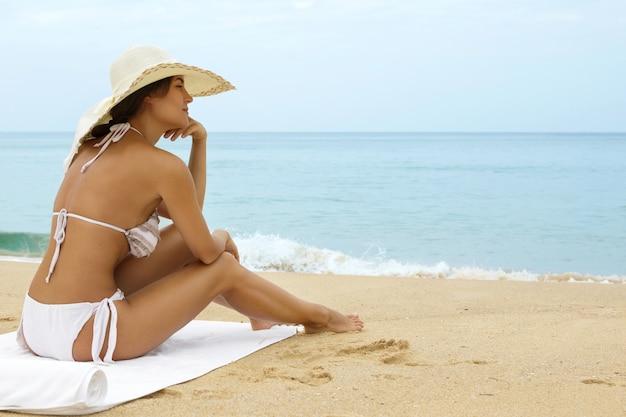 ビーチ帽子をかぶっている女性は海のそばに座っています。