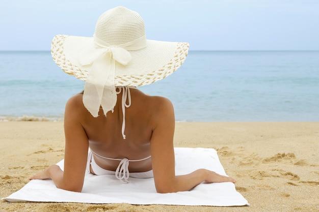 ビーチに座っている帽子の女