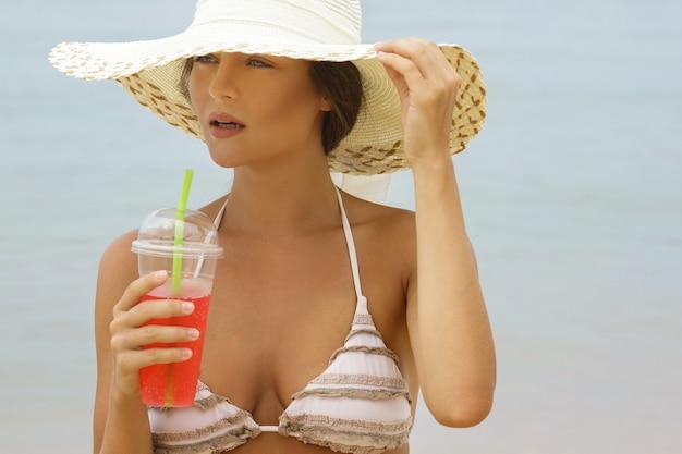 カクテルとビーチ帽子の女