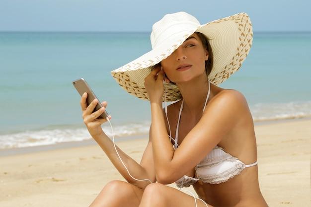 Красивая женщина слушает музыку на пляже
