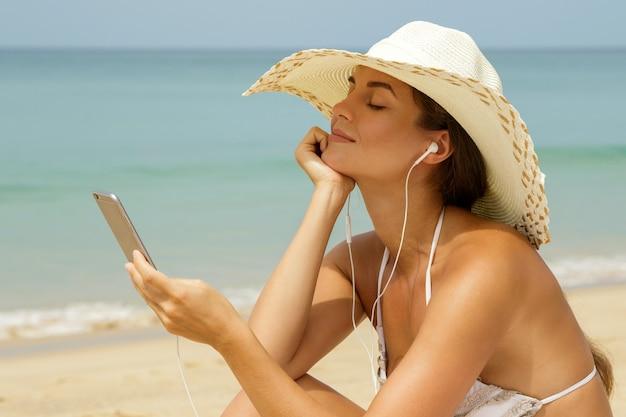 美しい女性がビーチで音楽を聴く