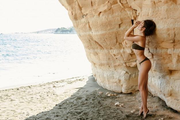 砂の崖の横にある女性