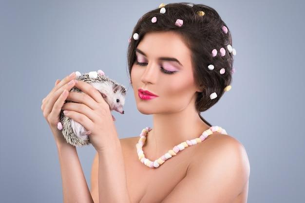 美しい女性はかわいいハリネズミを保持しています。