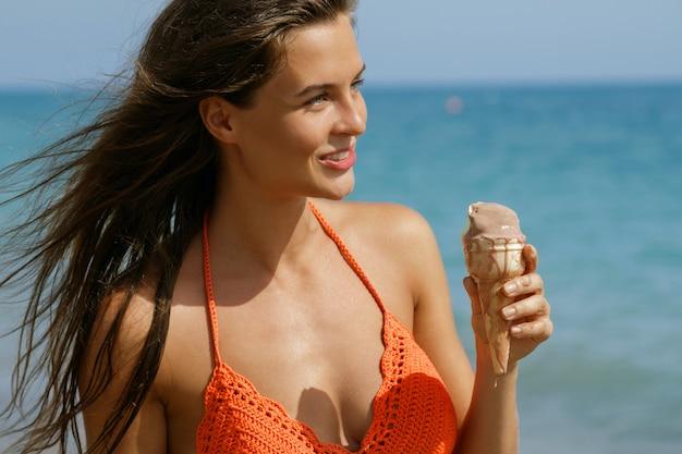 ビーチでアイスクリームコーンを持つ女性