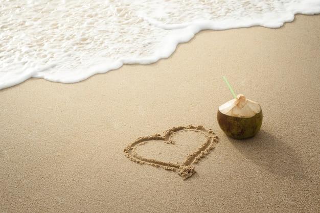 ココナッツの飲み物と砂の上に描かれた心