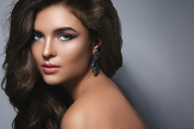 Великолепная женщина с красивым макияжем и прической