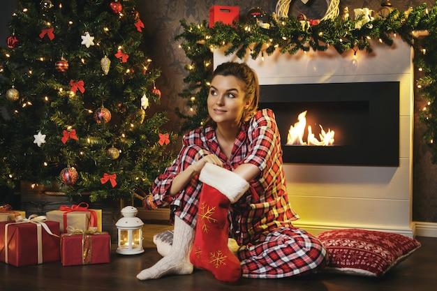 Женщина ищет подарки в рождественский чулок