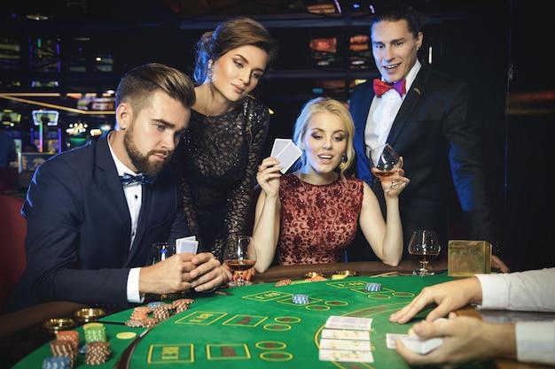 Группа богатых людей играет в покер в казино