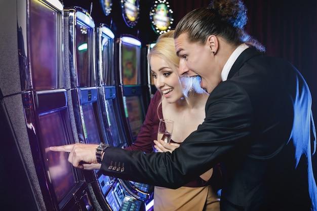 若いカップルのカジノでスロットマシンをプレイ