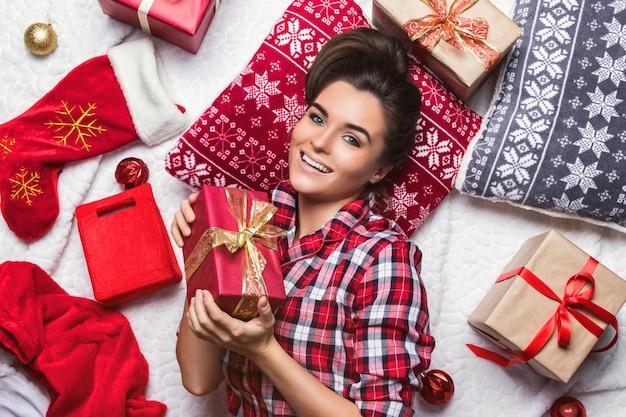Счастливая женщина с большим количеством рождественских подарков