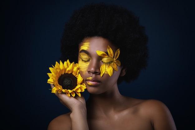 ひまわりと彼女の顔に創造的な化粧品でアフリカの女性