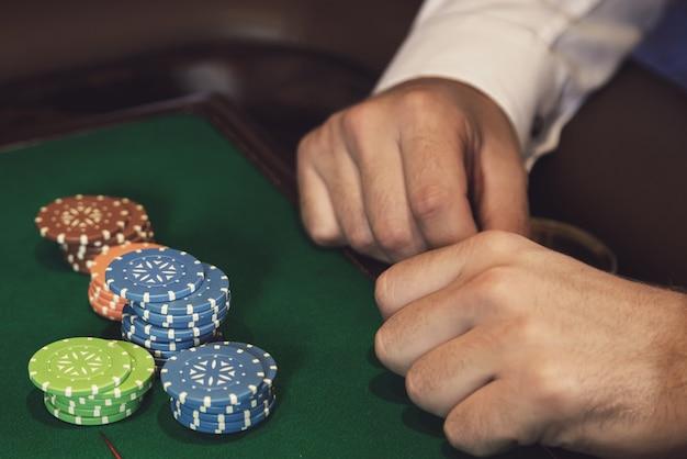Мужские руки и фишки казино