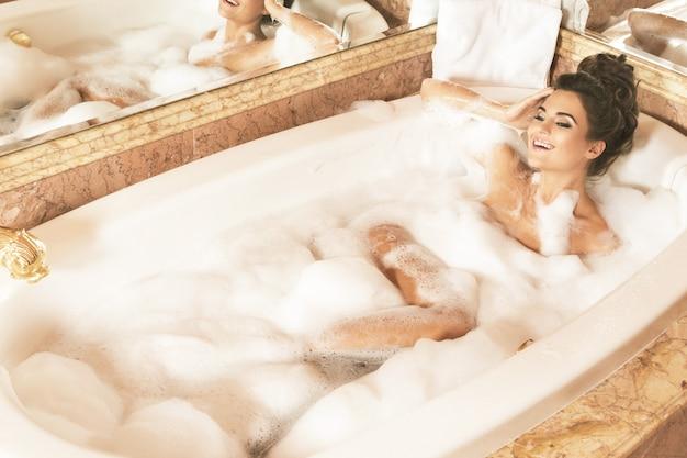幸せで美しい女性は泡で入浴しています