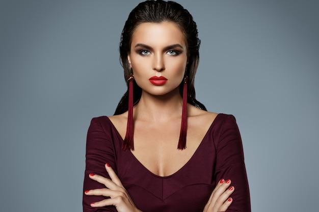 長い赤いイヤリングを身に着けている美しい化粧品で見事な女性