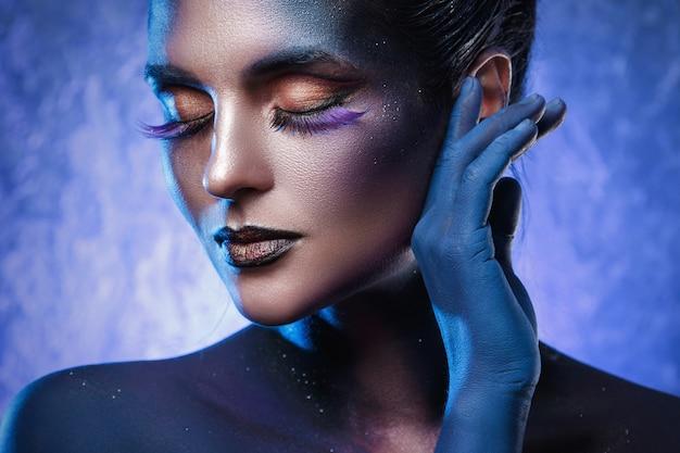 Красивая женщина с креативным макияжем и боди-артом