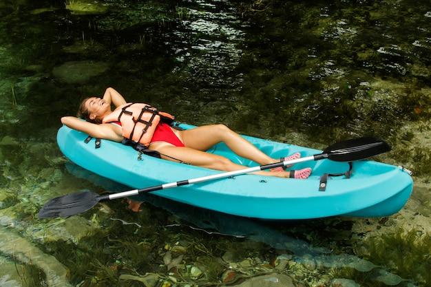 幸せな女はカヤックに横たわっている間にリラックスします。