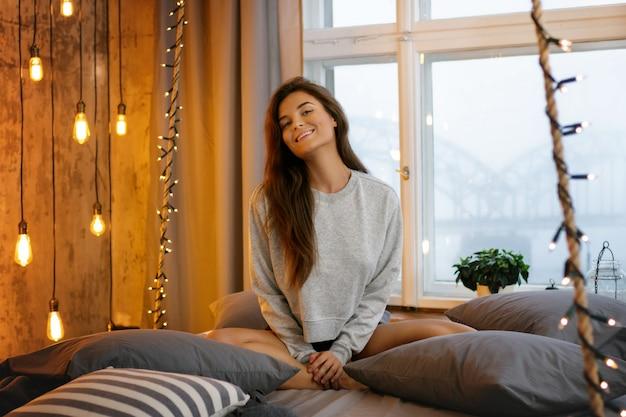居心地の良い部屋のベッドの上の若くてセクシーな女性