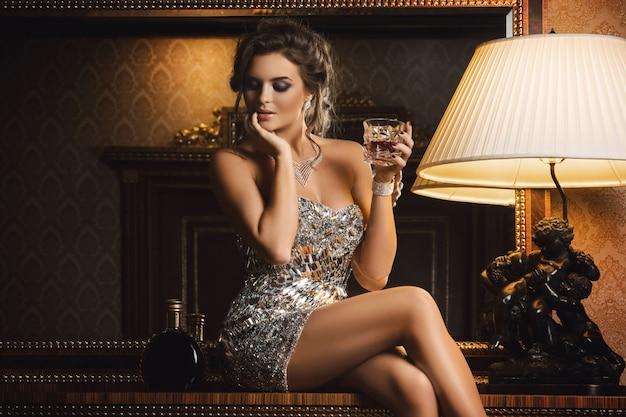 コニャックのグラスを持つ見事な女性