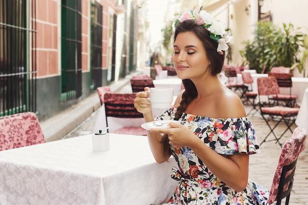 Счастливая женщина, сидя в уличном кафе с чашкой горячего кофе