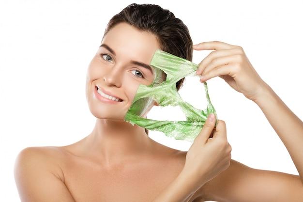 Женщина с зеленой отшелушивающей маской на лице