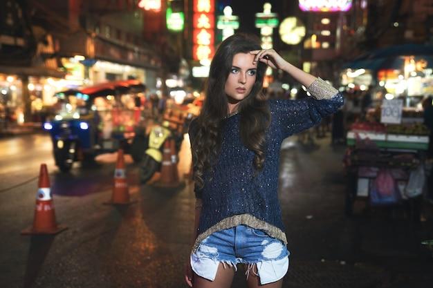 セクシーで美しいモデルがチャイナタウンでポーズをとっている