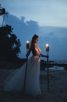 ビーチで松明と美しい花嫁