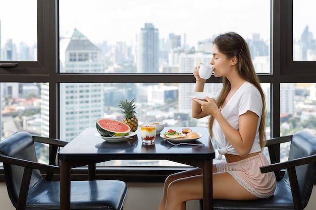 朝の朝食を食べる若い女性