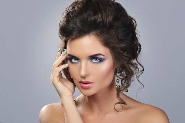 Женщина носит красивые серьги с драгоценными камнями