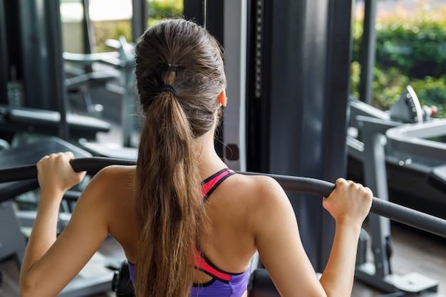 彼女の背中のために運動をしている女性-ラットプルダウン